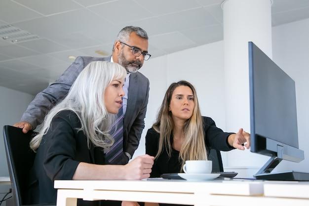 Bedrijfsgroep presentatie op pc-monitor kijken en project bespreken, zittend op de werkplek met kopje koffie en wijzend op display. zakelijke communicatie concept