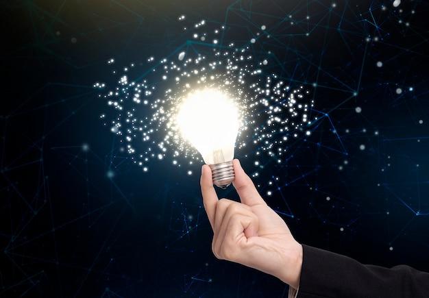 Bedrijfshand die gloeilamp, concept nieuwe ideeën met innovatie en creativiteit houden.