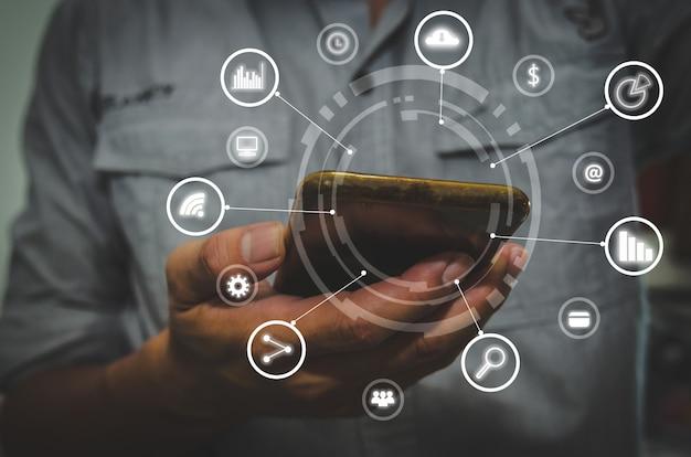 Bedrijfshand die smartphone met pictogrammenconcept gebruikt