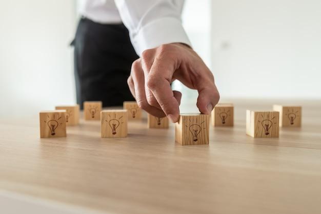 Bedrijfsidee en visieconcept - zakenman die vele houten kubussen met gloeilamppictogram plaatsen op bureau.
