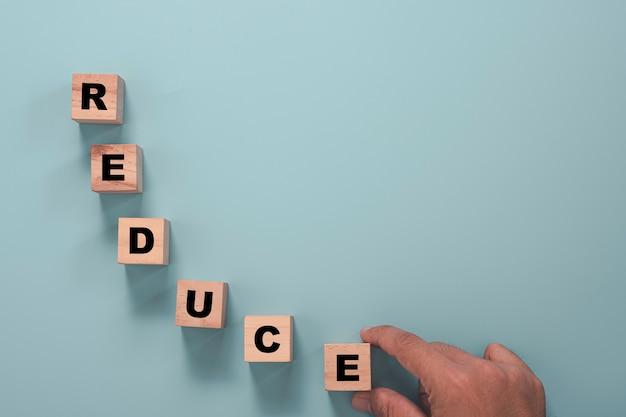 Bedrijfsinvesteringen verminderen en crisisconcept, zakenman die een houten kubusblok houdt dat het scherm afdrukt, verwoordt de formulering op een blauwe achtergrond.