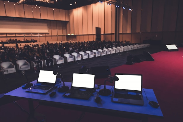 Bedrijfslaptop en microphotone bij podium in seminarieruimte