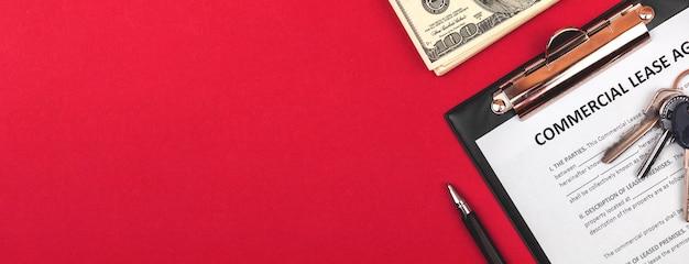 Bedrijfslease formulier. klembord met officieel aanvraagformulier. tafel met geld en huissleutels. rode achtergrond fotobanner met kopie ruimte
