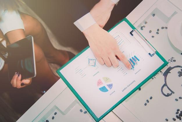 Bedrijfsleider die aan samenvattend rapport richten en grafiekplannen analyseren