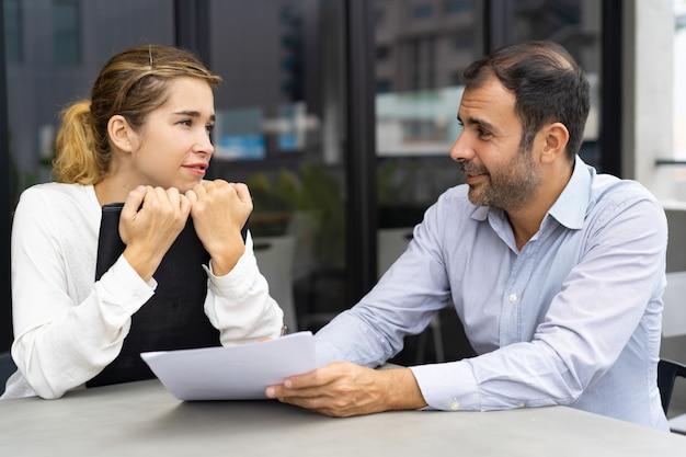 Bedrijfsleider en zijn vrouwelijke assistent die taken bespreken