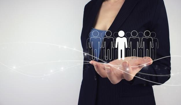 Bedrijfsleider, teamleider concept. hand houden digitale hologram groep mens met leider op grijze achtergrond. leider en ceo, teamleider concept