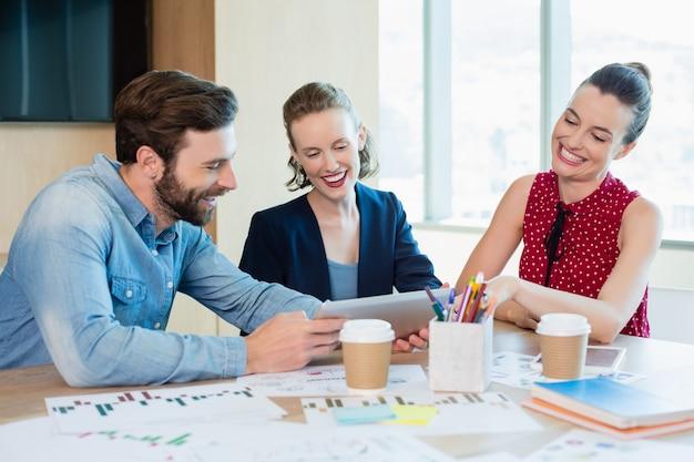 Bedrijfsleiders bespreken over digitale tablet in vergaderruimte
