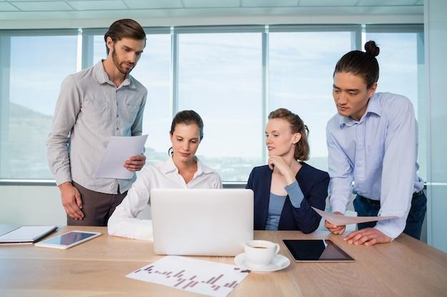 Bedrijfsleiders bespreken over laptop in vergaderruimte