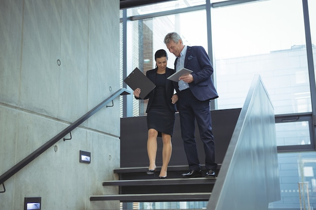 Bedrijfsleiders bespreken via digitale tablet op trappen