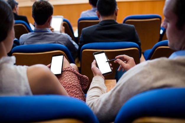 Bedrijfsleiders die deelnemen aan een zakelijke bijeenkomst met behulp van mobiele telefoon