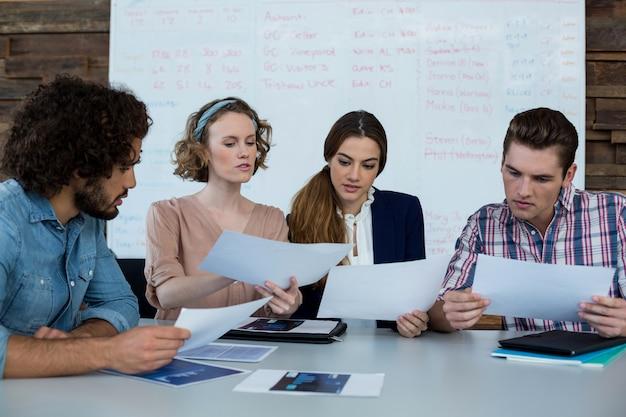 Bedrijfsleiders die over document in vergadering bespreken