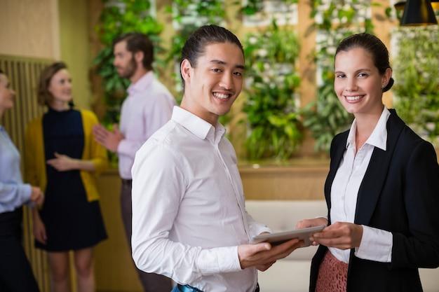 Bedrijfsleiders glimlachen tijdens het gebruik van digitale tablet op kantoor