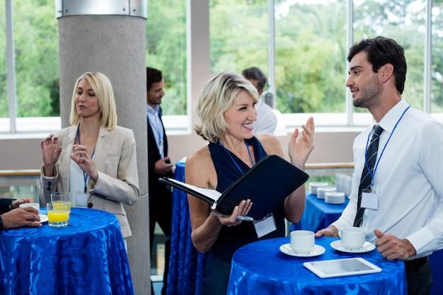 Bedrijfsleiders interactie met elkaar terwijl het hebben van koffie
