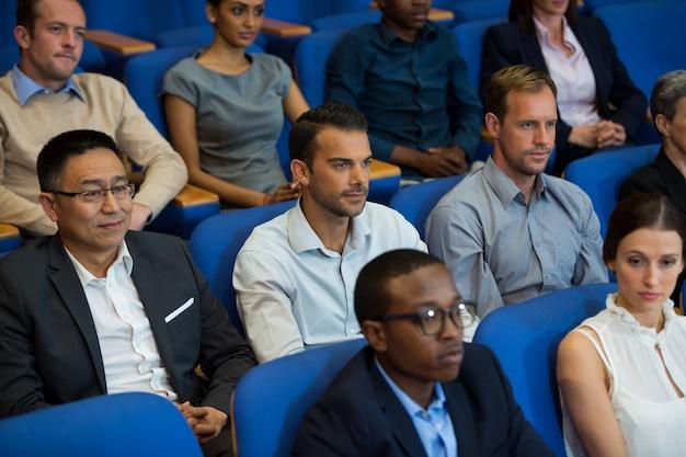 Bedrijfsleiders luisteren naar toespraak op conferentiecentrum