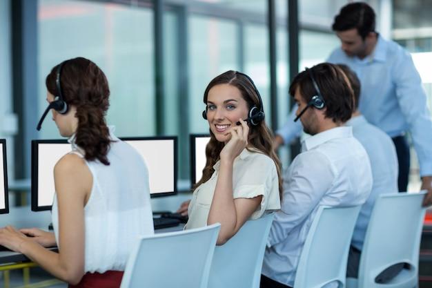 Bedrijfsleiders met headsets met behulp van computer
