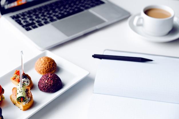 Bedrijfslunch in bureau, voedselsnacks coockies op wit houten bureau dichtbij laptop computer.