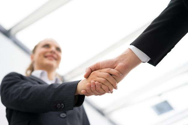Bedrijfsman en vrouwenhanddruk op kantoor