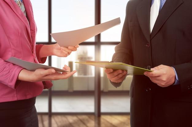 Bedrijfsman en vrouwenhandholdingsklembord en document