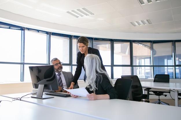 Bedrijfsmanagers rapporteren aan vrouwelijke baas. ondernemers zitten aan de vergadertafel met papier te houden en te praten. zakelijke discussie of teamwerk concept