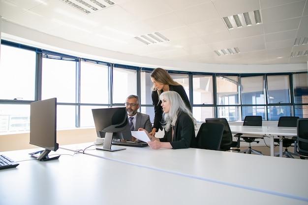 Bedrijfsmanagers verzamelen zich in de vergaderruimte, bekijken samen de projectpresentatie op een computermonitor en houden een papieren rapport vast. zakelijke communicatie of teamwerk concept