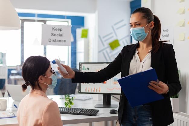 Bedrijfsmedewerker houdt sociale afstand en scant collega-temperatuur met infraroodthermometer om infectie met virus te voorkomen tijdens wereldwijde pandemie met covid-19. het controleren van de gezondheidszorg van kantoorwo