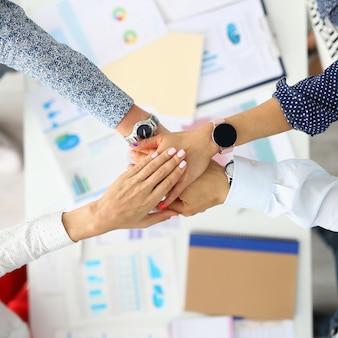 Bedrijfsmedewerkers vouwden hun handen samen over de werktafel.