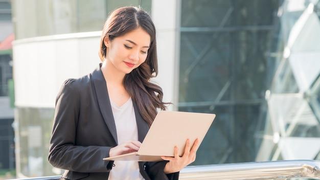 Bedrijfsmeisje met computernotitieboekje en stad