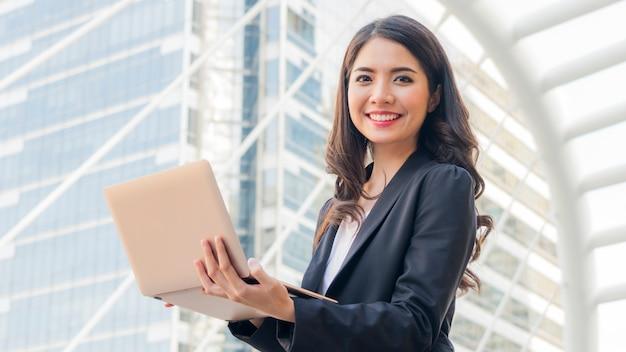 Bedrijfsmeisje met computernotitieboekje en stadsachtergrond.
