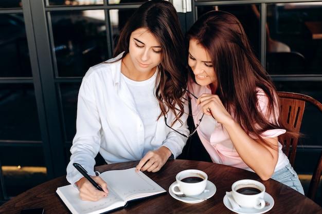 Bedrijfsmeisjes die in koffie werken, die iets belangrijk in kladblok neerschrijven