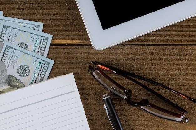 Bedrijfsmening van hierboven over een houten lijst - lege notitieboekje en pen, dollarrekeningen, glazen