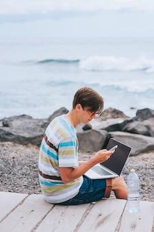 Bedrijfsmens die aan het strand met laptop werken