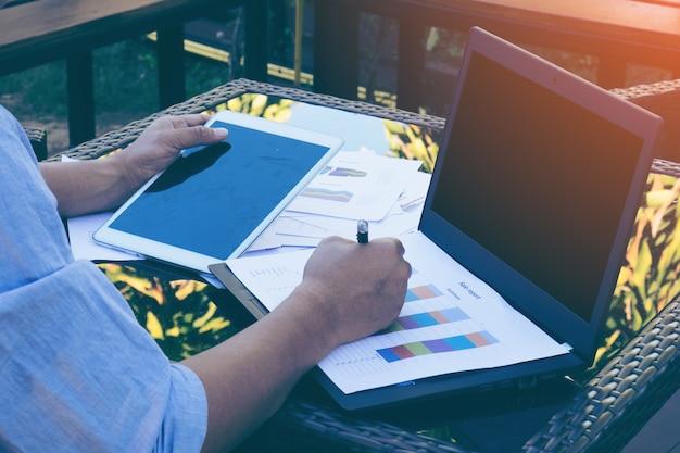 Bedrijfsmens die bij terras met tablet en documenten aan zijn bureau werken