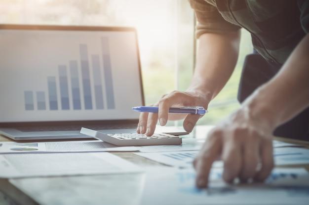 Bedrijfsmens die calculator gebruiken om balans jaarlijks met het gebruiken van laptop computer te herzien