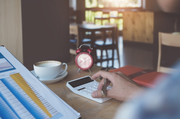 Bedrijfsmens die calculator gebruiken om balans jaarlijks met holdingspen te herzien en laptop computer met behulp van