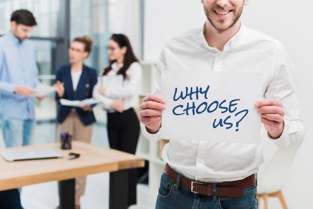Bedrijfsmens die een document met de vraag houdt waarom voor ons kiezen