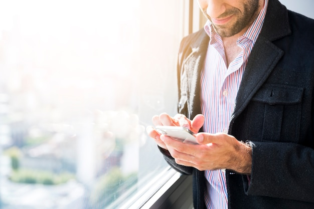 Bedrijfsmens die een mobiele telefoon met behulp van
