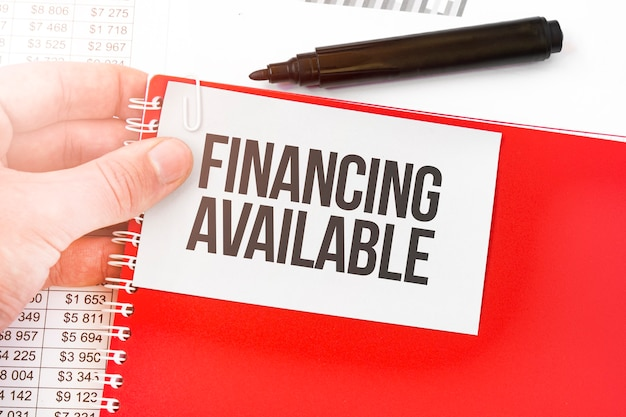 Bedrijfsmens die een rood notitieboekje en een witte kaart met beschikbare tekst financiering houden. financieel concept