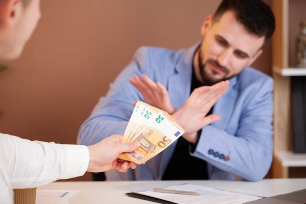 Bedrijfsmens die geld weigert om steekpenningen het concept corruptie en antiomkoping te nemen