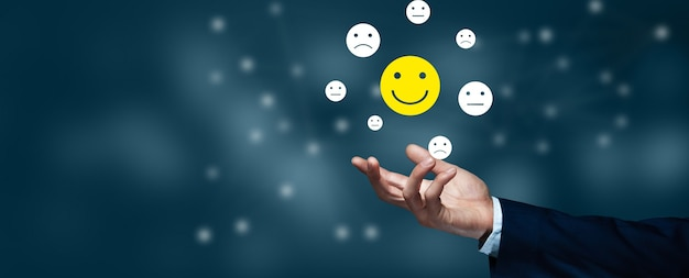 Bedrijfsmens die het glimlachen gezichtspictogrammen houden