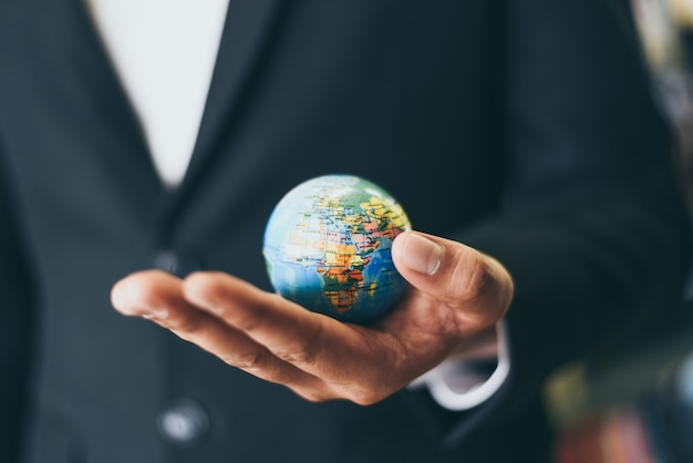 Bedrijfsmens die het model van de aardebol in hand houden en - globaal zaken en reis rond de wereld of red het wereldconcept
