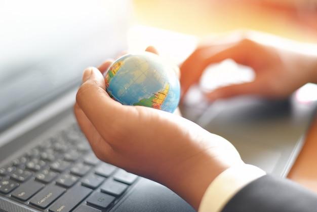 Bedrijfsmens die het model van de aardebol in hand houden en laptop gebruiken - bedrijfstechnologie globaal en rond de wereldconcept
