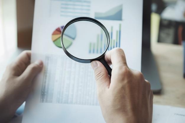 Bedrijfsmens die het overdrijven gebruiken om jaarlijkse balans met het gebruiken van laptop computer aan het berekenen van begroting te herzien. audit en controleer integriteit vóór investering concept.