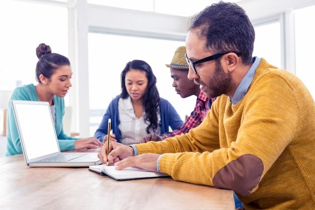 Bedrijfsmens die in boek schrijven terwijl het zitten met collega's in creatief bureau