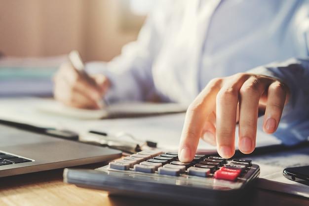 Bedrijfsmens die in bureau werken en calculator gebruiken