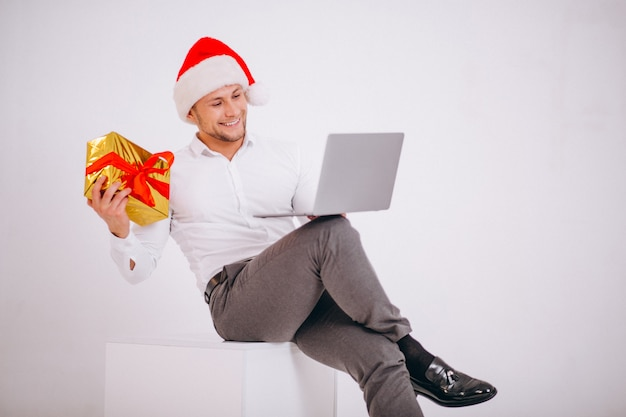Bedrijfsmens die in santahoed online op kerstmis winkelt