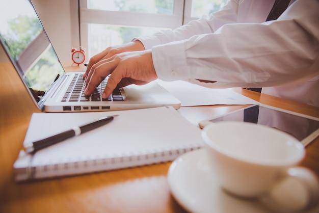 Bedrijfsmens die laptop computer met behulp van. mannelijke hand die op laptop toetsenbord typen