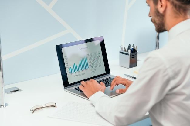 Bedrijfsmens die laptop met behulp van om financiële gegevens te analyseren