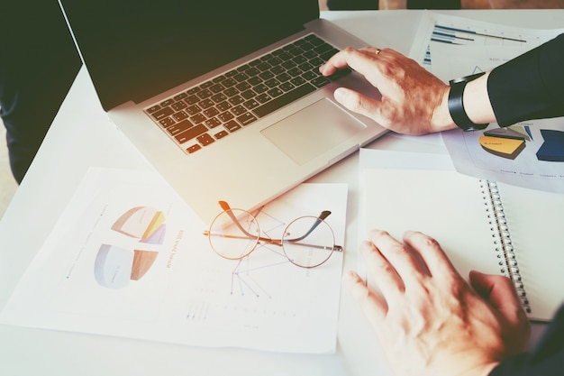 Bedrijfsmens die laptop met rapportgrafiek gebruiken in bureau die nieuw bedrijfsproject plannen