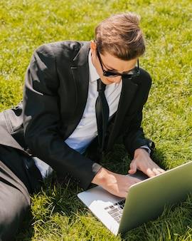 Bedrijfsmens die laptop op groen gras met behulp van