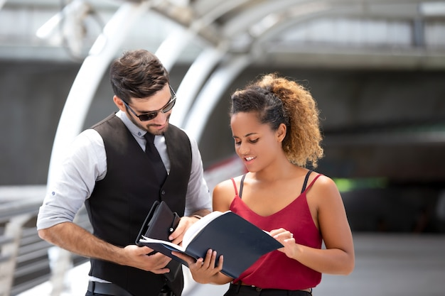 Bedrijfsmens die met collega bespreken terwijl status op voetgangersbrug
